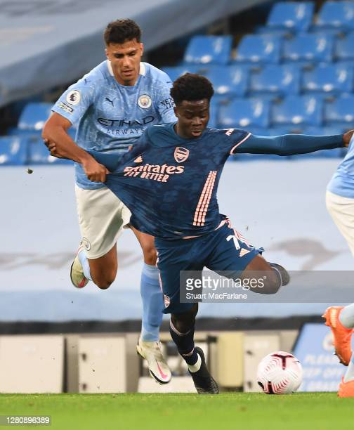 Bukayo Saka of Arsenal held back by Rodrigo of Man City during the Premier League match between Manchester City and Arsenal at Etihad Stadium on...