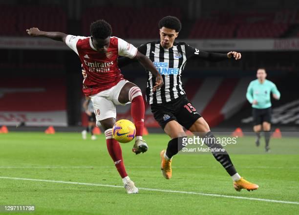 Bukayo Saka of Arsenal holds off Jamal Lewis of Newcastle United during the Premier League match between Arsenal and Newcastle United at Emirates...