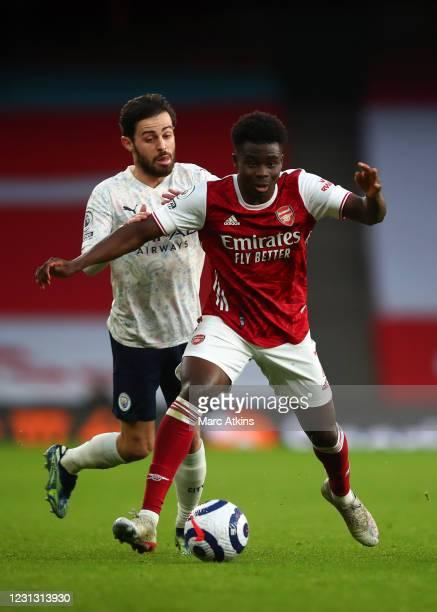 Bukayo Saka of Arsenal in action with Bernardo Silva of Manchester City during the Premier League match between Arsenal and Manchester City at...