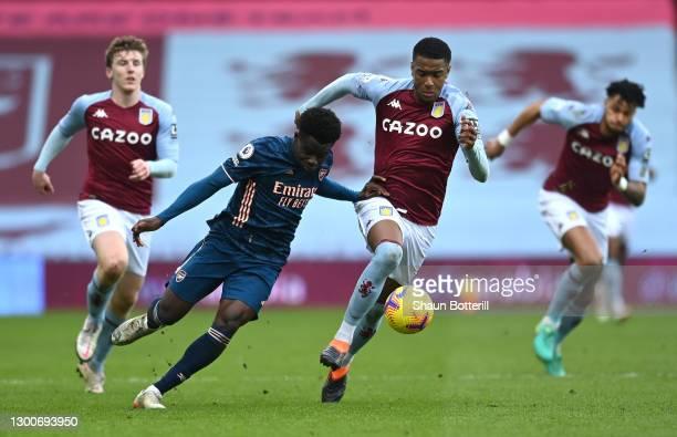 Bukayo Saka of Arsenal is challenged by Ezri Konsa of Aston Villa during the Premier League match between Aston Villa and Arsenal at Villa Park on...