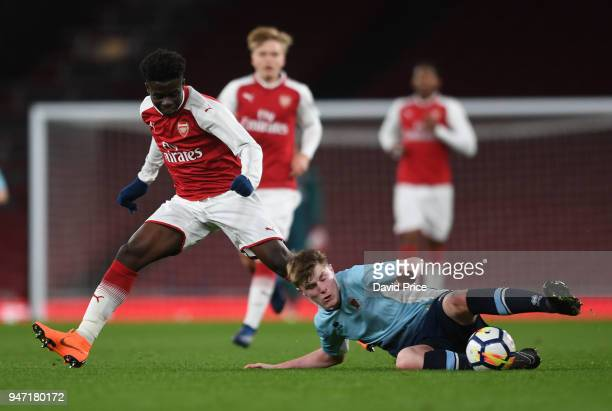 Bukayo Saka of Arsenal is tackled by Brendan O'Brien of Blackpool during the match between Arsenal and Blackpool at Emirates Stadium on April 16 2018...