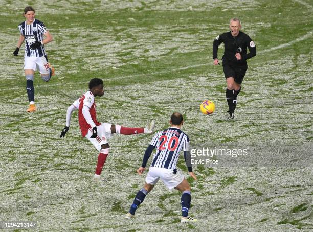 Bukayo Saka of Arsenal passes the ball under pressure from Branislav Ivanovic of WBA during the Premier League match between West Bromwich Albion and...