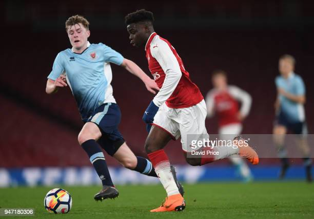 Bukayo Saka of Arsenal runs at Brendan O'Brien of Blackpool during the match between Arsenal and Blackpool at Emirates Stadium on April 16 2018 in...