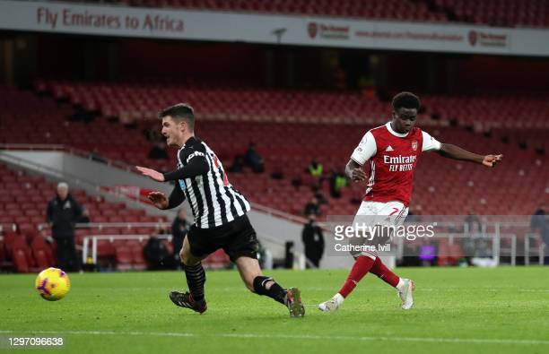 Bukayo Saka of Arsenal scores their team's second goal past Ciaran Clark of Newcastle United during the Premier League match between Arsenal and...
