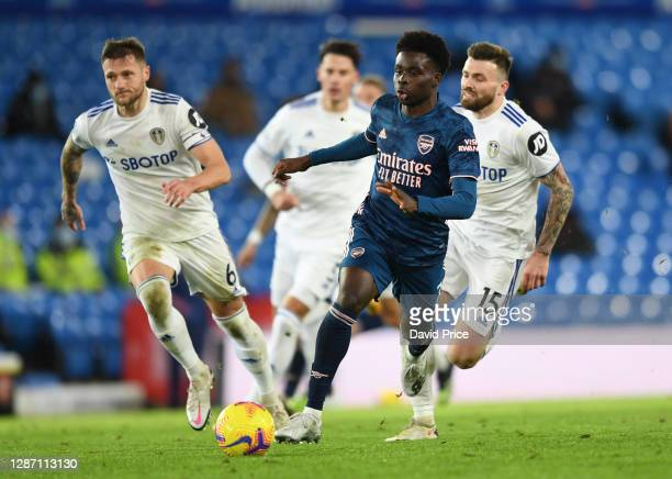 Bukayo Saka of Arsenal takes on Liam Cooper and Stuart Dallas of Leeds during the Premier League match between Leeds United and Arsenal at Elland...