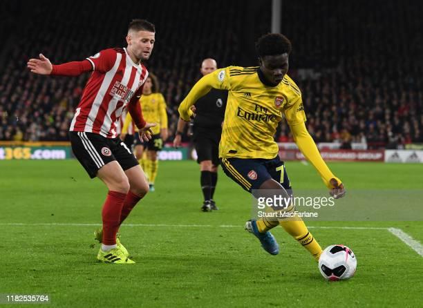 Bukayo Saka of Arsenal takes on Ollie Norwood of Sheff United during the Premier League match between Sheffield United and Arsenal FC at Bramall Lane...