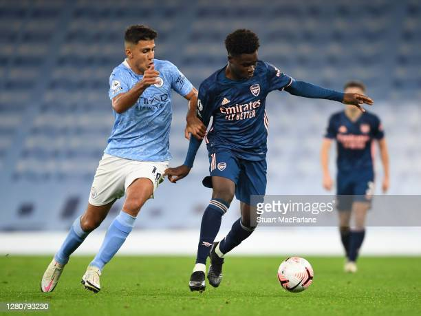 Bukayo Saka of Arsenal takes on Rodrigo of Man City during the Premier League match between Manchester City and Arsenal at Etihad Stadium on October...