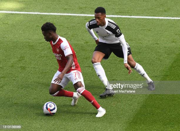 Bukayo Saka of Arsenal takes on Tosin Adarabioyo of Fulham during the Premier League match between Arsenal and Fulham at Emirates Stadium on April...