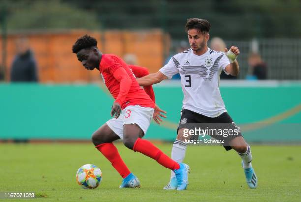 Bukayo Saka of England and Kaan Kurt of Germany compete during the international friendly match between U19 Germany and U19 England at...
