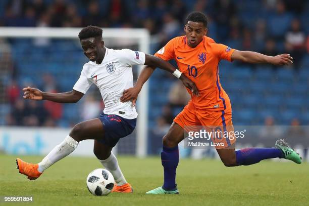Bukayo Saka of England and Quinten Maduro of the Netherlands challenge for the ball during the UEFA European Under17 Championship Semi Final match...