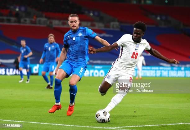 Bukayo Saka of England and Sverrir Ingi Ingason of Iceland in action during the UEFA Nations League group stage match between England and Iceland at...
