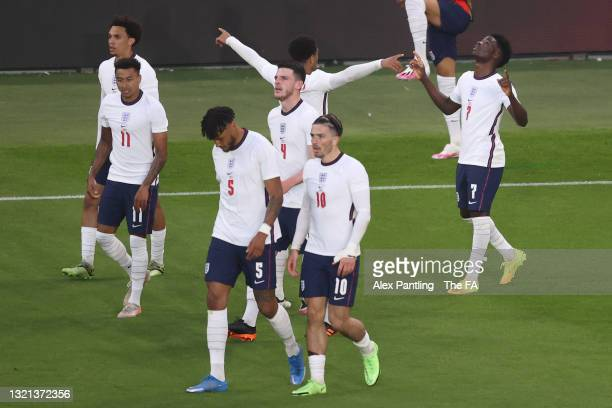 Bukayo Saka of England celebrates with team mates after scoring their side's first goal during the international friendly match between England and...