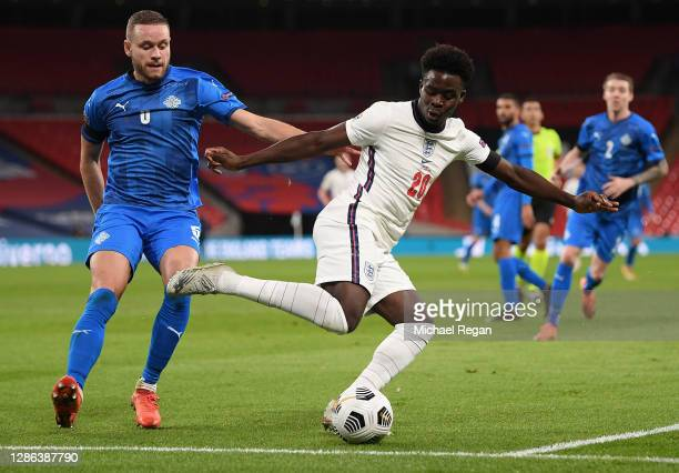 Bukayo Saka of England is challenged by Sverrir Ingason of Iceland during the UEFA Nations League group stage match between England and Iceland at...