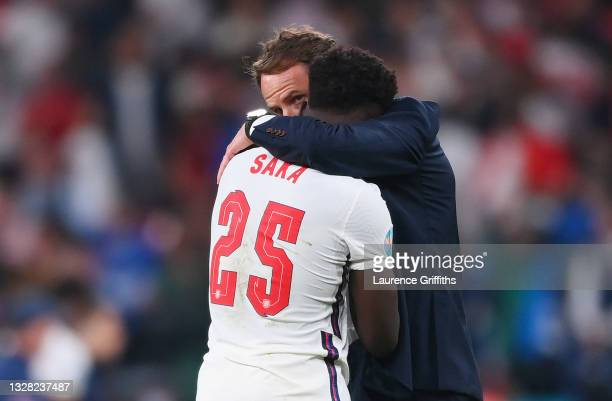 Bukayo Saka of England is consoled by Gareth Southgate, Head Coach of England following defeat in the UEFA Euro 2020 Championship Final between Italy...