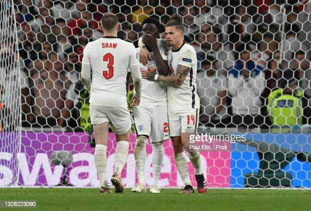 Bukayo Saka of England is consoled by Luke Shaw and Kalvin Phillips after missing their side's fifth penalty in the penalty shoot out during the UEFA...