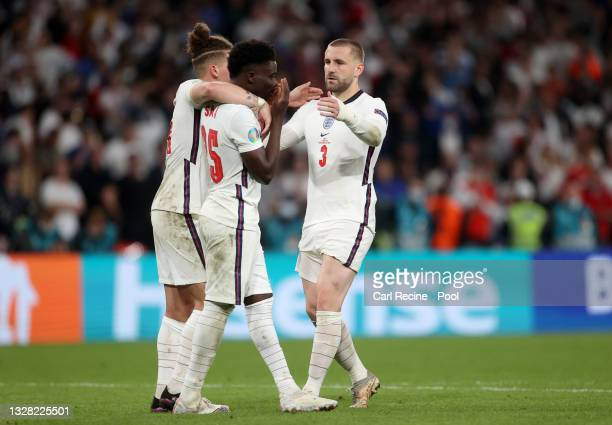 Bukayo Saka of England is consoled by teammates Kalvin Phillips and Luke Shaw after having their team's fifth penalty saved in a penalty shoot out...