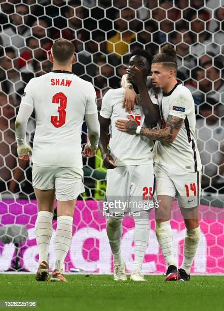 Bukayo Saka of England is consoled by teammates Luke Shaw and Kalvin Phillips following the UEFA Euro 2020 Championship Final between Italy and...