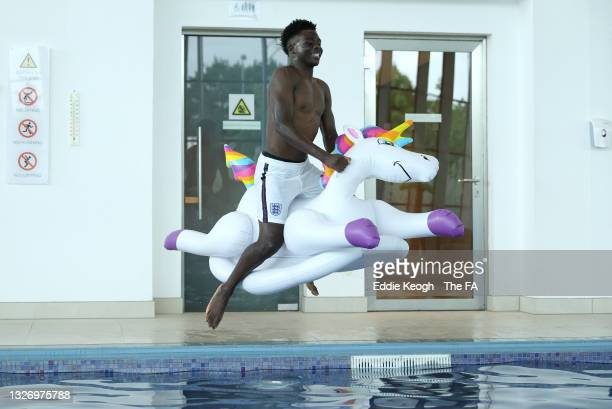 Bukayo Saka of England jumps into the swimming pool on an inflatable unicorn at St George's Park on July 04, 2021 in Burton upon Trent, England.