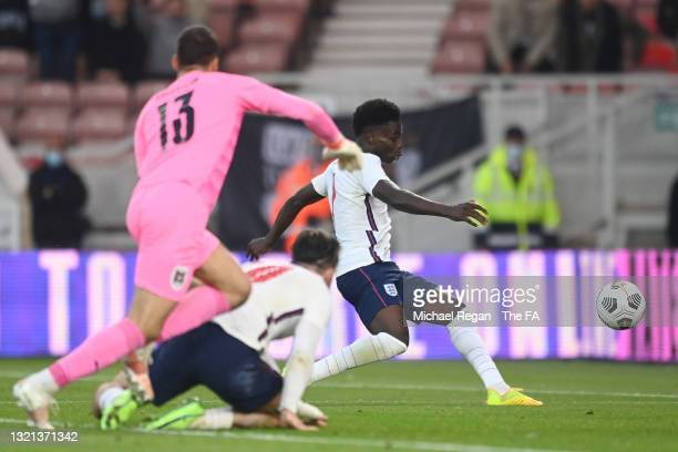 Bukayo Saka of England scores their sides first goal past Daniel Backmann of Austria during the international friendly match between England and...
