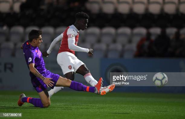 Bukayo Saka scores Arsenal's 1st goal under pressure from Adam Lewis of Liverpool during the match between Arsenal U23 and Liverpool U23 at Meadow...
