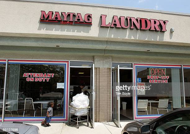 Bukola Abioye and her 21monthold son Fawaz Ilumoka enter a Maytagequipped laundromat with their laundry June 22 2005 in Glenview Illinois Chinese...