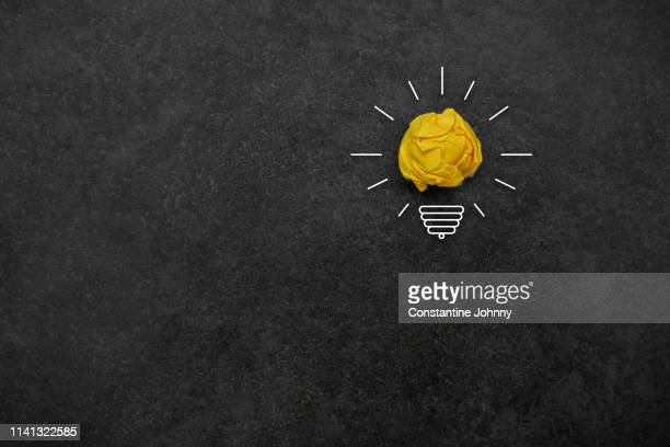 bulb concepts with yellow crumpled paper ball - idea fotografías e imágenes de stock