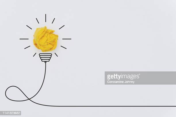 bulb concepts with yellow crumpled paper ball - innovation stock pictures, royalty-free photos & images