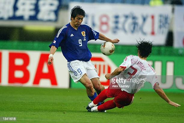 Bulent Korkmaz of Turkey tackles Akinori Nishizawa of Japan during the 1st half of the Japan v Turkey World Cup Second Round match played at the...