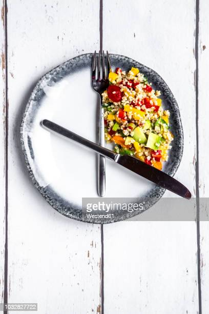 bulgar salad on round plate, symbol for intermittent fasting - fasting activity stock pictures, royalty-free photos & images