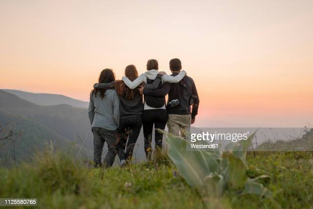 bulgaria, balkan mountains, group of hikers standing on viewpoint at sunset - geloof stockfoto's en -beelden
