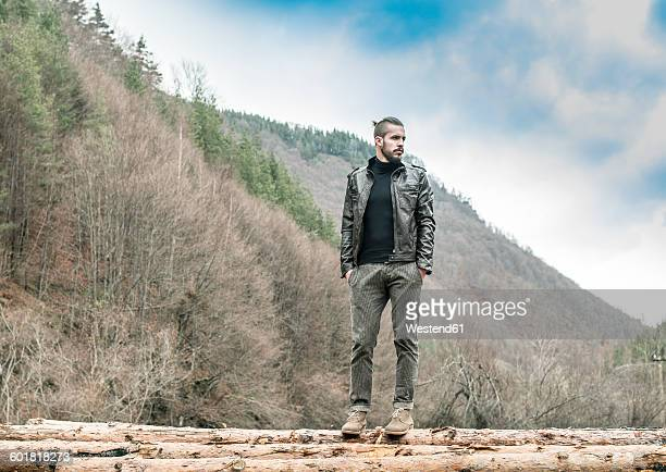 Bulgaria, Rhodope Mountains, young man standing on logs