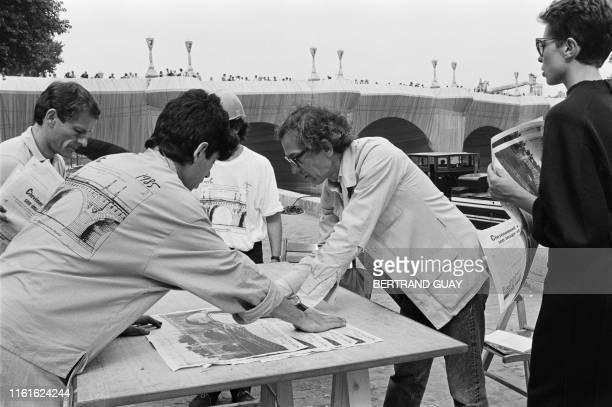 US Bulgarian born wrapping artist Christo autographs on September 23 1985 doublepage of Paris daily Libération carrying his drawing of wrapped Pont...