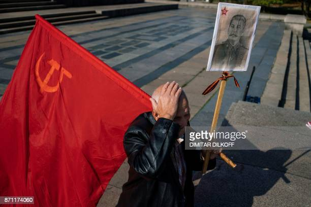 A Bulgarian Communist supporter holds the red flag of the Soviet union and a portrait of Soviet dictator Josef Stalin in front of the monument of the...