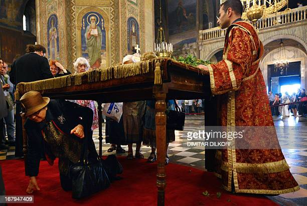 A Bulgarian EasternOrthodox believer passes under a table on which a Bible is placed during the Good Friday service in the goldendomed Alexander...