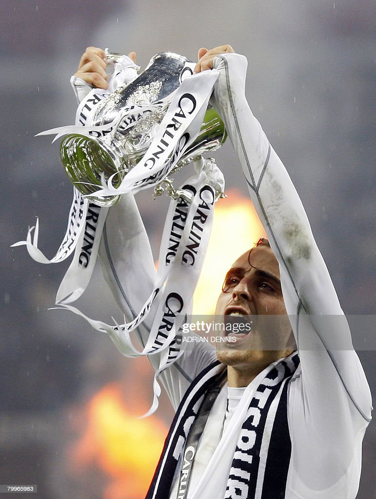 Bulgarian player Dimitar Berbatov celebrates with the trophy after Tottenham Hotspur won the Carling Cup Final against Chelsea at Wembley Stadium in London on February 24, 2008. Tottenham Hotspur won the game 2-1 after Jonathan Woodgate scored an extra time goal. AFP PHOTO ADRIAN DENNIS Mobile and website use of domestic English football pictures are subject to obtaining a Photographic End User Licence from Football DataCo Ltd Tel : +44 (0) 207 864 9121 or e-mail accreditations@football-dataco.com - applies to Premier and Football League matches.