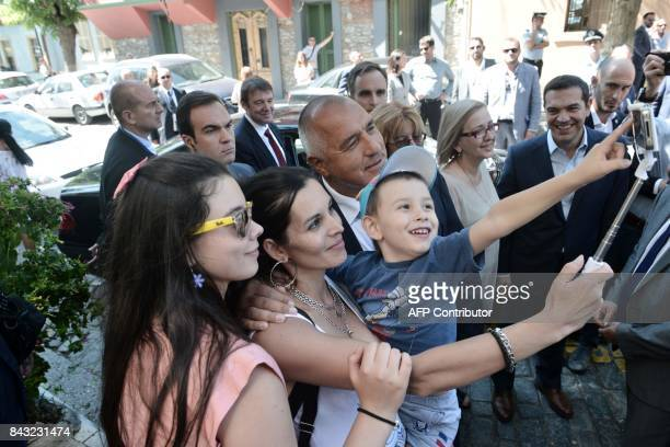 Bulgarian Prime minister Boyko Borisov poses for a selfie with Bulgarian tourists as Greek Prime Minister Alexis Tsipras looks on after the ceremony...