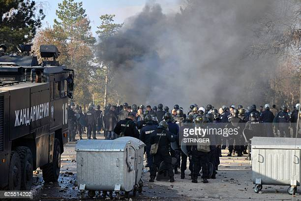 Bulgarian riot police stand near garbarge bins during clashes in the migrants reception centre in the town of Harmanli on November 24 2016 About 1500...
