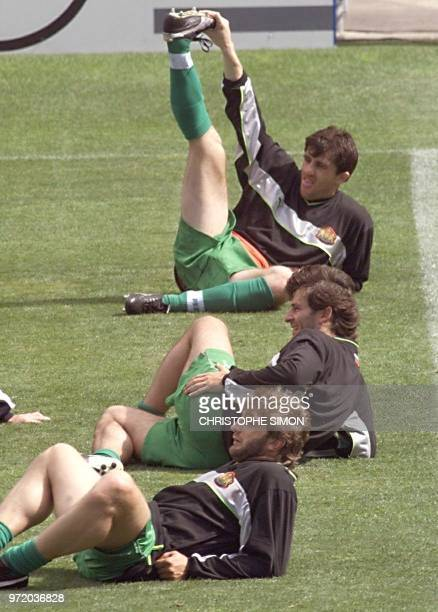 Bulgarian soccer player Ivaylo Yordanov stretches as teammates Trifon Ivanov and Emil Kostadinov relax 11 June during a training session at the...