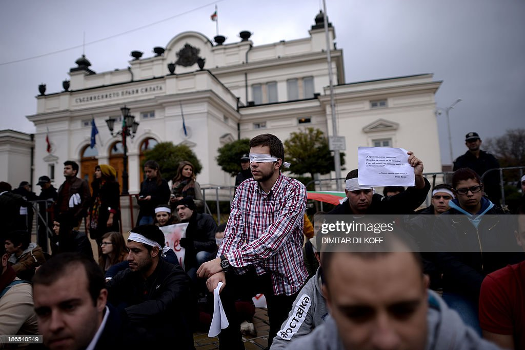 Bulgarian students, one of them wearing a bandage on his eyes, stage a protest in front of the Parliament building in Sofia on November 1, 2013. Students marching in Bulgarian capital called for the beleaguered Socialist-backed government's ousting, amid continuing protests and occupations in universities around the country.