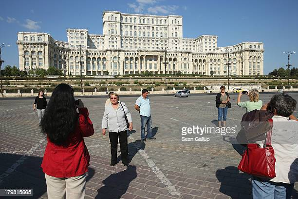 Bulgarian tourists photograph one another in front of the Palace of the Parliament built by former Romanian dictator Nicolae Ceausescu on September 7...