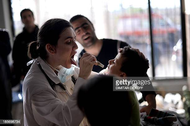 Bulgarian volunteer doctor examines on October 19 2013 a Syrian refugee boy at the recently opened Vrazhdebna shelter in Sofia a former school that...