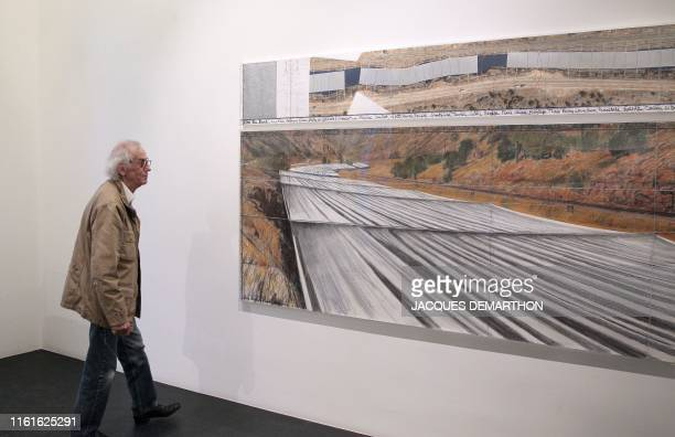 Bulgarianborn artist Christo poses on November 26 2010 next to one of his works as part of his exhibition Project for the Arkansas River State of...