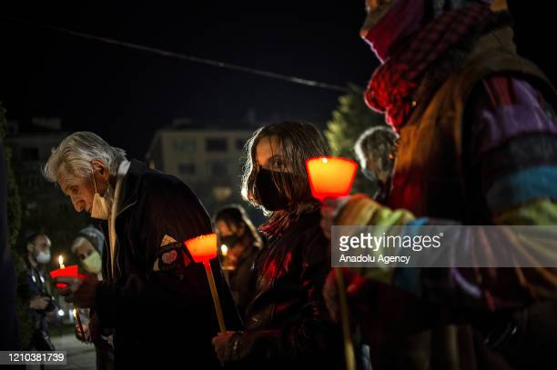 Bulgarians wearing protective face masks due to the coronavirus pandemic hold candles during an Orthodox Easter service in front of the Seven Saints...