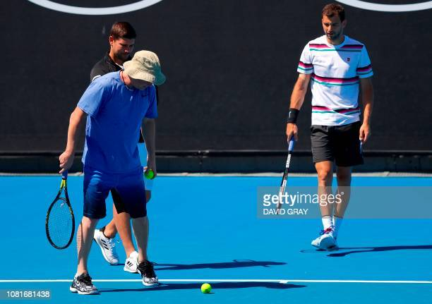 Bulgaria's Grigor Dimitrov and his coach Andre Agassi inspect the court during a practice session ahead of the Australian Open tennis tournament in...