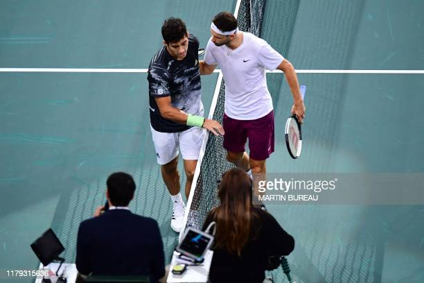 Bulgaria's Grigor Dimitrov consoles Chile's Christian Garin after winning during their men's singles quarterfinal tennis match at the ATP World Tour...