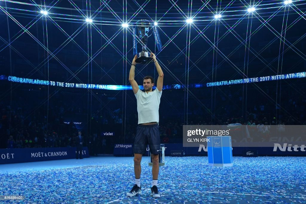 TOPSHOT - Bulgaria's Grigor Dimitrov holds the trophy as he celebrates winning his men's singles final match against Belgium's David Goffin on day eight of the ATP World Tour Finals tennis tournament at the O2 Arena in London on November 19, 2017. Dimitrov won the match 7-5, 6-4, 6-3. / AFP PHOTO / Glyn KIRK