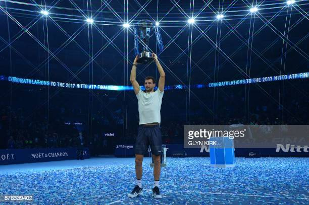 TOPSHOT Bulgaria's Grigor Dimitrov holds the trophy as he celebrates winning his men's singles final match against Belgium's David Goffin on day...