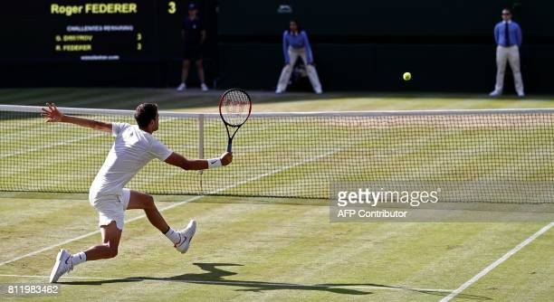 Bulgaria's Grigor Dimitrov returns against Switzerland's Roger Federer during their men's singles fourth round match on the seventh day of the 2017...