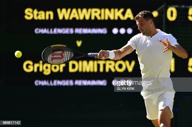 Bulgaria's Grigor Dimitrov returns to Switzerland's Stan Wawrinka during their men's singles first round match on the first day of the 2018 Wimbledon...