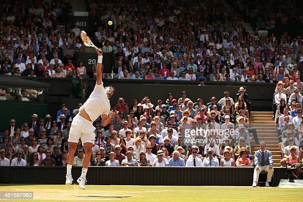 Bulgaria's Grigor Dimitrov serves to Britain's Andy Murray during their men's singles quarterfinal match on day nine of the 2014 Wimbledon...